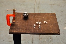 3D printed plastic, metal ball bearing, plywood and stain, G-clamp, powder-coated steel stand